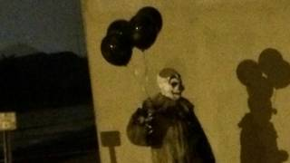Creepy clown with black balloons wandering Wisconsin