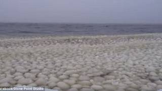 Thousands of mysterious snowballs wash up in waves on a Maine lake